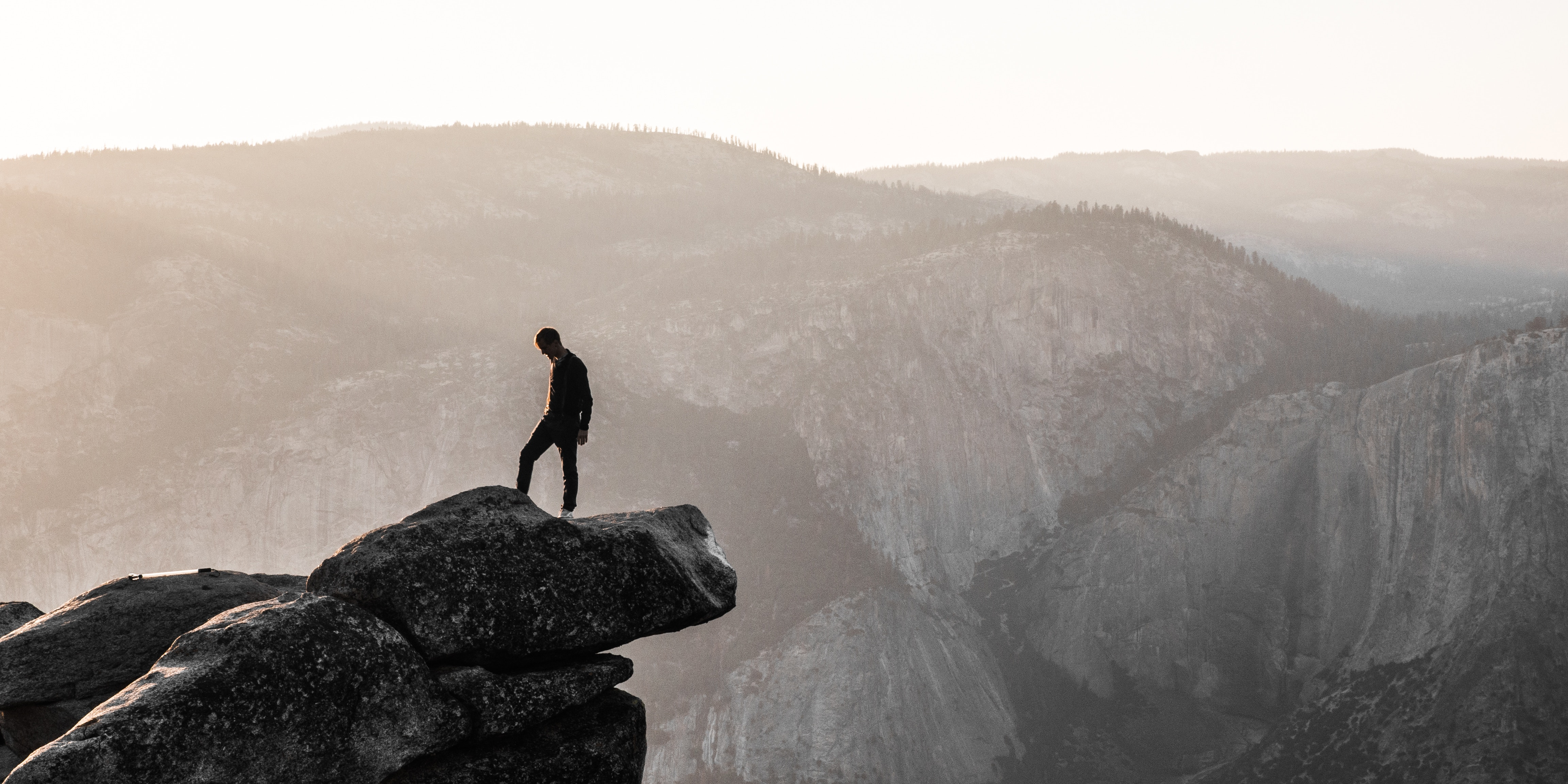 Hiker standing on a cliff in the mountains