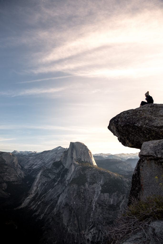 Person sitting on a rock on a cliff