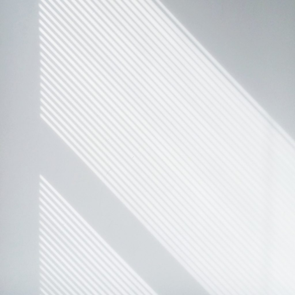 White wall with mini blind slat shadows