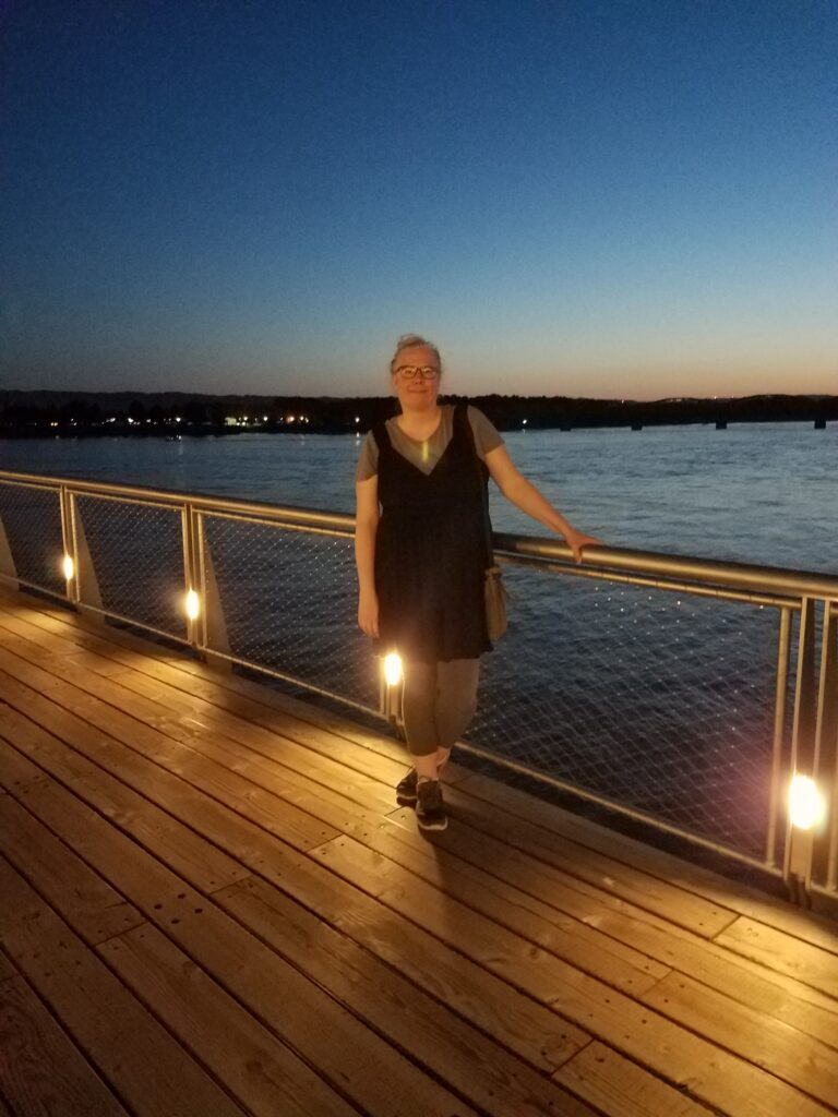 Author of post standing on a boardwalk overlooking a river in the evening