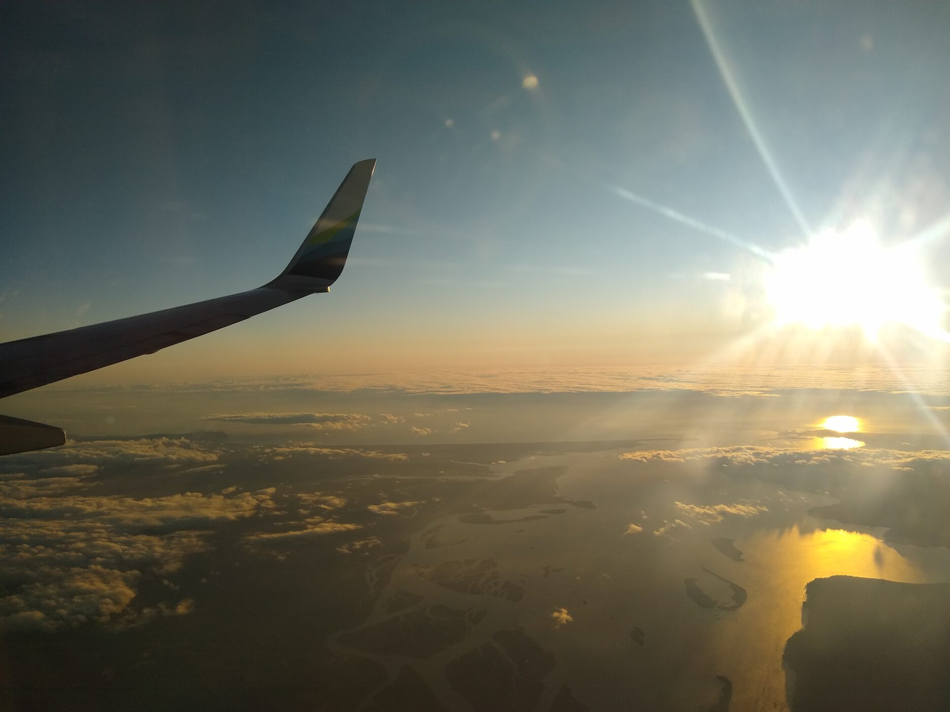 Airplane wing over clouds and mountains as the sun rises. Travel rewards cards will take us to Alaska on a budget