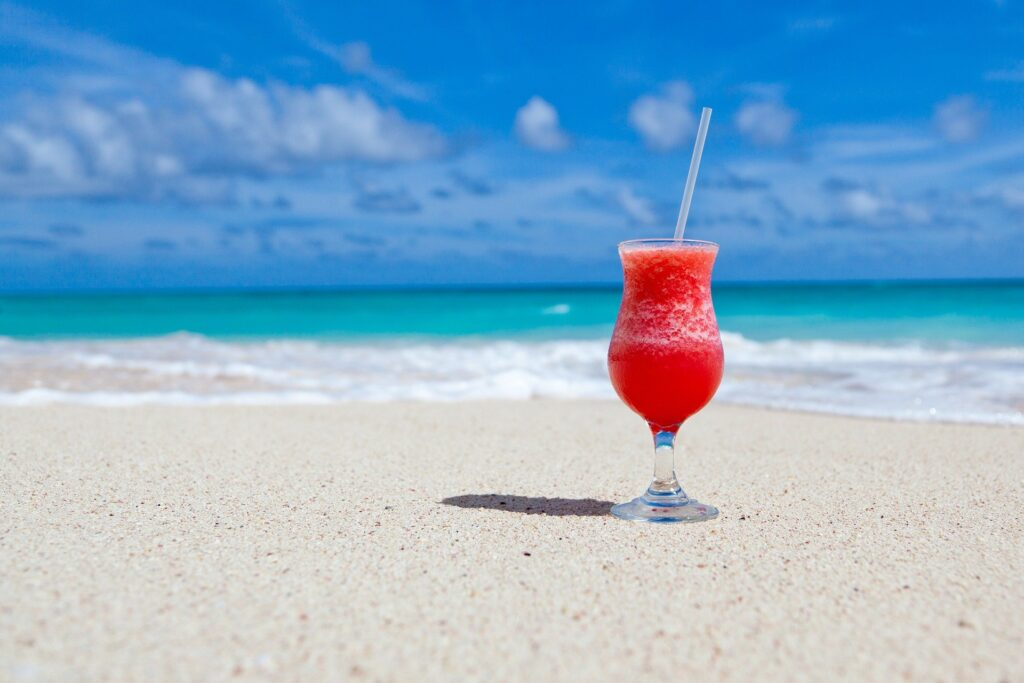 Fruity drink on sandy beach. You can use travel rewards cards without going broke
